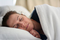 Woman sleeping in bed. Comfortable woman sleeping in bed. Relaxation concept. Real people. Copy space royalty free stock photography