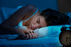 Woman Sleeping. In a bed in a dark bedroom stock image