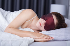 Woman sleeping on bed with eye mask Royalty Free Stock Images