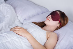 Woman sleeping on bed with eye mask Stock Photos