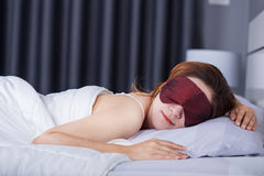 Woman sleeping on bed with eye mask Royalty Free Stock Image