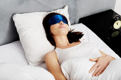 Woman sleeping in bed with eyes band. Stock Images