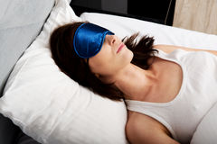 Woman sleeping in bed with eyes band. Stock Image