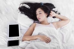 Woman sleeping on bed with gadget Stock Image