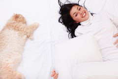 Woman sleeping on the bed with her cat Stock Photos