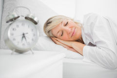 Woman sleeping in bed peacefully Stock Images