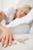Woman sleeping in bed with pills in foreground Stock Image