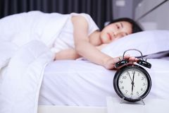 Woman sleeping on bed and rise hand to turn off alarm clock in b. Woman sleeping on bed and rise hand to turn off alarm clock in the bedroom Royalty Free Stock Photos