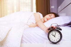 Woman sleeping on bed and rise hand to turn off alarm clock in b. Woman sleeping on bed and rise hand to turn off alarm clock in the bedroom Royalty Free Stock Photography