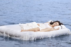 Woman sleeping on the bed in the sea Stock Image