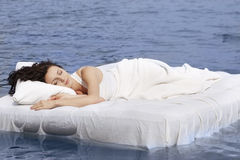 Woman sleeping on the bed in the sea Stock Images