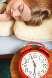 Woman sleeping in bed with set alarm clock. Royalty Free Stock Photography