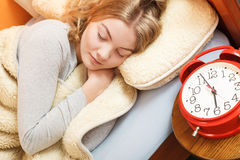 Woman sleeping in bed with set alarm clock. Stock Image