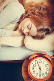 Woman sleeping in bed with set alarm clock. Royalty Free Stock Images