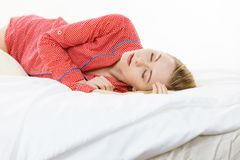 Woman sleeping in bed on the side. Relax rest sleep positions concept. Girl drowning in dreams. Young woman wearing red dotted pajamas lying in bed on the side royalty free stock photography