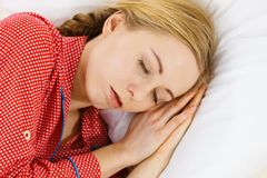 Woman sleeping in bed on the side. Relax rest sleep positions concept. Girl drowning in dreams. Young woman wearing red dotted pajamas lying in bed on the side royalty free stock photo