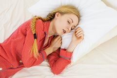 Woman sleeping in bed on the side. Relax rest sleep positions concept. Girl drowning in dreams. Young woman wearing red dotted pajamas lying in bed on the side stock images