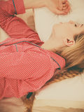 Woman sleeping in bed on the side. Relax rest sleep positions concept. Girl drowning in dreams. Young woman wearing red dotted pajamas lying in bed on the side royalty free stock photos