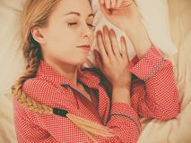 Woman sleeping in bed on the side. Relax rest sleep positions concept. Girl drowning in dreams. Young woman wearing red dotted pajamas lying in bed on the side royalty free stock images