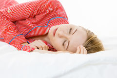 Woman sleeping in bed on the side. Relax rest sleep positions concept. Girl drowning in dreams. Young woman wearing red dotted pajamas lying in bed on the side stock image