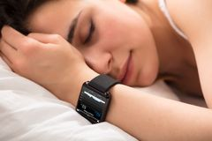 Heart Beat Monitor On Smart Watch. Woman Sleeping On Bed With Smart Watch Showing Heartbeat Monitor Stock Image