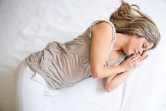 Woman sleeping on a bed Stock Photos