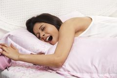 Woman sleeping on the bed and yawning Royalty Free Stock Photos