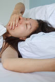 Woman sleeping in bed Stock Images