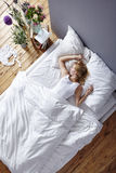 Woman sleeping in bed. Young woman laying in bed view from above morning atmosphere Royalty Free Stock Image