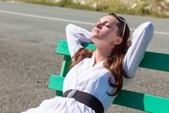 A woman is sleeping on the bench Stock Image