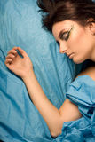 Woman sleeping in blue bedclothes. Woman sleeping blue studio lighting makeup eyes closed dreams bedclothes stock image