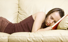 Woman sleeping on book at home Stock Photo