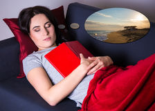 Woman sleeping with book on sofa at home and dreaming about vaca Stock Photos