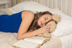 Woman sleeping  with a book and a teddy bear Royalty Free Stock Photos