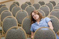 Woman sleeping at boring conference Royalty Free Stock Photos