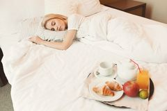 Woman sleeping while the breakfast is ready. Woman sleeping while healthy breakfast is ready. Traveller relaxing after hard day, copy space, selective focus Royalty Free Stock Photo