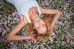 Woman sleeping on cherry blossoms Stock Photography