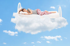 Woman sleeping on a comfortable bed in the clouds. Relaxed young woman sleeping on a comfortable bed in the clouds Stock Image