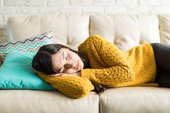 Woman Sleeping Comfortably In Living Room. Beautiful woman taking break for short sleep in middle of day at home royalty free stock photos