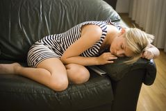 Woman Sleeping on Couch. Woman curled up and napping on a couch Stock Photos