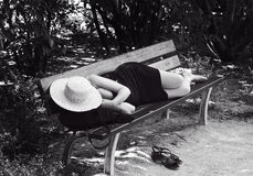 Woman sleeping on a desk on sunny day, dark sepia photo. Woman on siesta. Lunch time in Spain Stock Photo