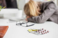 Woman sleeping on desk after taking pills stock photos