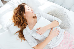 Woman sleeping with earphones on the bed. Attractive woman sleeping with earphones on the bed at home Stock Photography