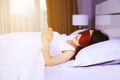 Woman sleeping with eye mask on bed Stock Images