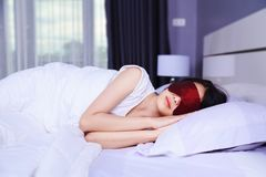 Woman sleeping with eye mask on bed Royalty Free Stock Images