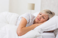 Woman sleeping with eyes closed in bed. Pretty mature woman sleeping with eyes closed in the bed stock photo
