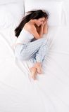 Woman sleeping in fetal position. Beautiful young woman sleeping in fetal position on white bed royalty free stock photos
