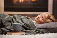 Woman sleeping beside fireplace. Woman sleeping at home lying on floor in front of a fire place Stock Photos