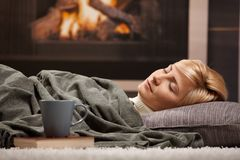 Woman sleeping beside fireplace. Woman sleeping at home lying on floor in front of a fire place Stock Image