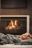 Woman sleeping beside fireplace. Woman sleeping at home lying on floor in front of a fire place Royalty Free Stock Images